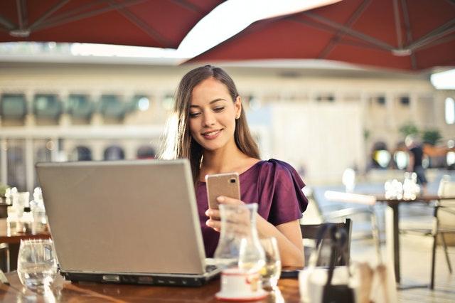woman-wearing-purple-shirt-holding-smartphone-white-sitting-826349